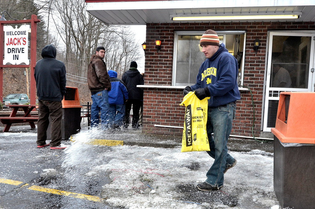 Description of . Mike McMahon - The Record, Josiah Deeb uses ice melter at Jack's Drive-In opens for it's 76th season in Wynantskill, Wednesday March 13, 2014.