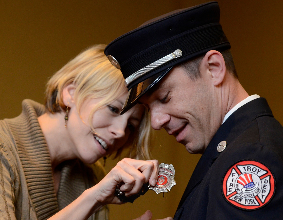 Description of . Mike McMahon - The Record,  Troy Fire Department promoted Matthew Dudek from Lieutenant to Captain, his wife Sarah pins his badge on him at the Hilton Garden Inn in Troy, Tuesday, November 19, 2013