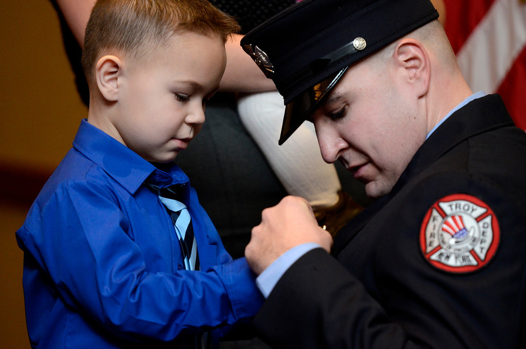 Description of . Mike McMahon - The Record,  Troy Fire Department promoted Ryan Handerhan from firefighter to Lieutenant, here his son Gavin pins his badge on at the Hilton Garden Inn in Troy, Tuesday, November 19, 2013