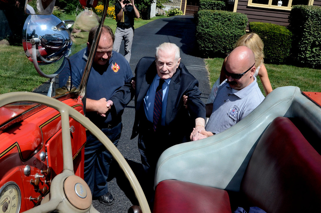 Description of . L-R Troy Firefighter Eric Wisher helps Frank J. Kennedy, with firefighter Mike DeForge. Frank J. Kennedy, the oldest living Troy firefighter, celebrated his 100th birthday (August 22) with a ride on an antique 1947 Mack fire truck to his last fire station on Canal Ave in Troy, N.Y., Sunday, August 25, 2013.. (Mike McMahon/The Record)