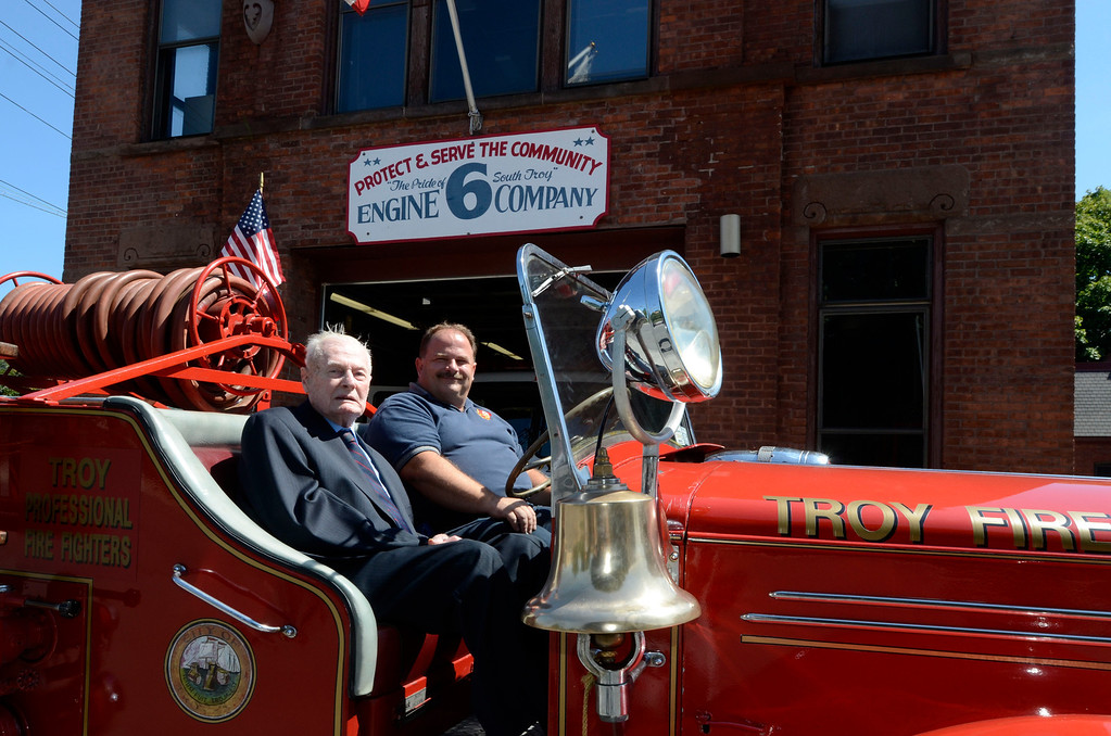 Description of . Frank J. Kennedy, here with Troy Firefighter Eric Wisher, the oldest living Troy firefighter, celebrated his 100th birthday (August 22) with a ride on an antique 1947 Mack fire truck to his last fire station on Canal Ave in Troy, N.Y., Sunday, August 25, 2013.. (Mike McMahon/The Record)