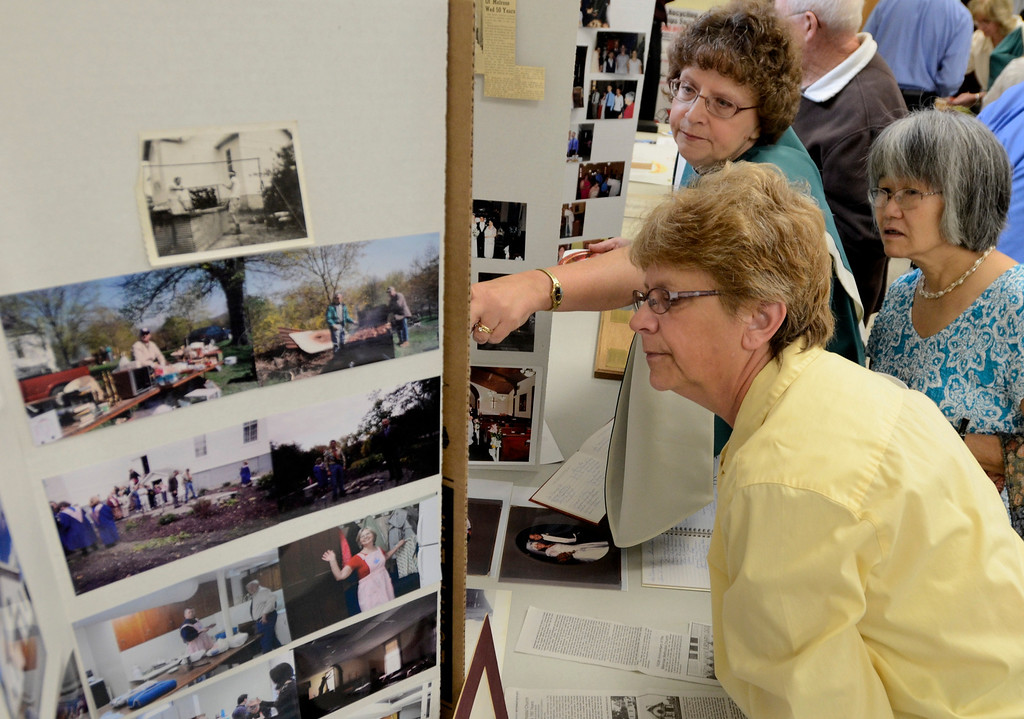 Description of . Mike McMahon - The Record,  Janet Harrington, Debbie Kalbfliesh and Mariko Drost look over photos at the  Melrose United Methodist Church 160th Anniversary, September 29, 2013.