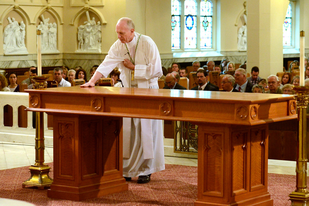 Description of . Mike McMahon - The Record, Rev. Howard J. Hubbard, D.D., Bishop of Albany anoints the new Altar with sacramental oils. St. Mary of the Assumption Parish celebrated 100 years with a mass at the Waterford Church, Sunday 10/06/2013.