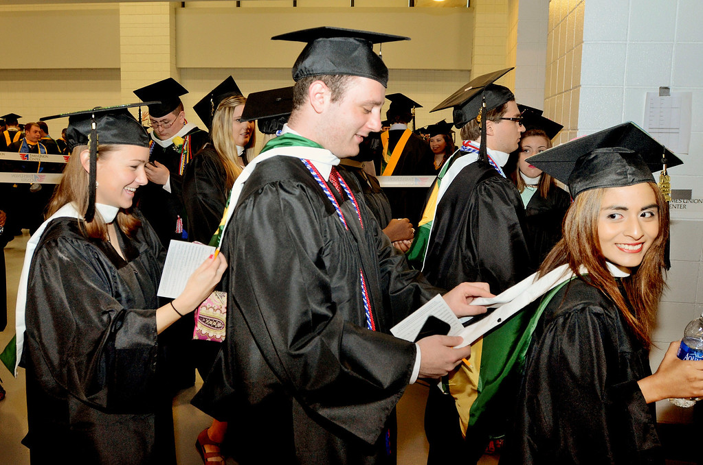 Description of . L-R Kaitlyn Buscone of Medfield Ma, Andrew Federico of Plainview NY and Catherine Dondero of Norwood Ma help each other out with gowns. Siena College commencement at the Times Union Center in Albany, Sunday  May 18,  2014 (Mike McMahon - The Record)