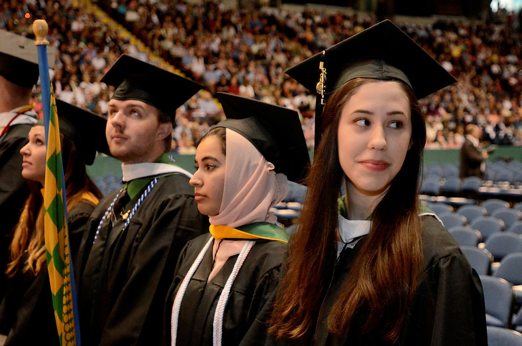 Description of . Emily A. Scimeca at right looks for family in the stands at Siena College commencement at the Times Union Center in Albany, Sunday  May 18,  2014 (Mike McMahon - The Record)