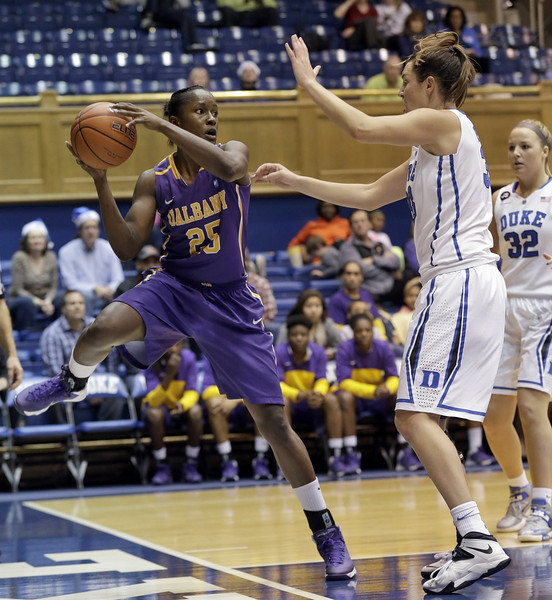 Description of . Albany's Shereesha Richards (25) looks to pass as Duke's Haley Peters defends at right during the second half of an NCAA college basketball game in Durham, N.C., Thursday, Dec. 19, 2013. Duke won 80-51. (AP Photo/Gerry Broome)