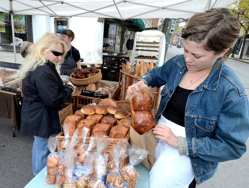 . Ani Mooney of Troy purchases cranberry orange brioche break from Megan McClean of the Placid Baker. The Troy Farmers Market goes outdoors for the 15th Summer Season, Saturday May 3, 2014 (Mike McMahon - The Record)