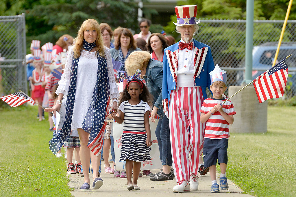 """. Mike McMahon - The Record ,  L-R School 14 Principal Karen Cloutier, Kiera Joyce, \""""Uncle Sam\"""" Fred Polnisch and Leo Christoper lead the 1st grade to Troy\'s School 14 celebrate \""""Red, White and Blue\"""" day to honor the flag and patriotism,  Friday June 6, 2014"""
