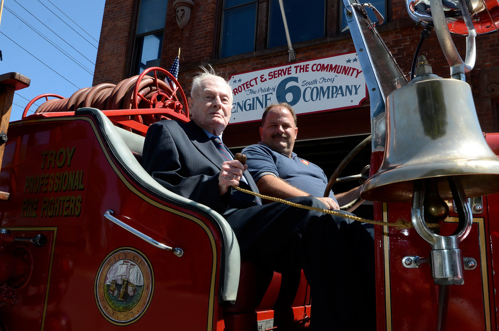 . Frank J. Kennedy, here with Troy Firefighter Eric Wisher, the oldest living Troy firefighter, celebrated his 100th birthday (August 22) with a ride on an antique 1947 Mack fire truck to his last fire station on Canal Ave in Troy, N.Y., Sunday, August 25, 2013.. (Mike McMahon/The Record)
